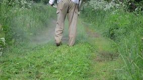 Closeup farmer cut grass. Closeup worker man farmer cut grass in garden with weed trimmer stock footage