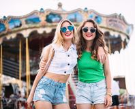 Closeup fashion lifestyle portrait of two pretty best friends girls, wearing bright swag style floral hats, mirrored sunglasses, h. Aving fun and make crazy stock image