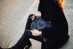 Closeup fashion portrait of young stylish hipster girl posing in the sunset, feminine look,a black coat,party bag,toned Stock Images