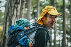 Closeup of father carries his child on his back in a backpack Stock Photo