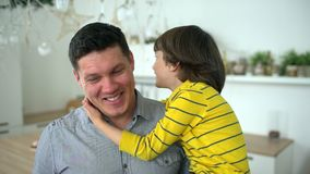 Portrait of son and father. Handsome young father holds his young son in his arms. A happy family. Father`s Day. slow stock footage