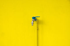 Closeup faucet on concrete Yellow wall background. Water leaking Royalty Free Stock Images