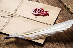Closeup of feather on envelope with red sealant and inkwell Stock Image