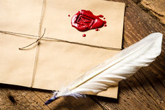Closeup of feather on envelope with red sealant and inkwell Stock Images