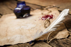 Closeup of a feather lying on old sheet of paper stock image