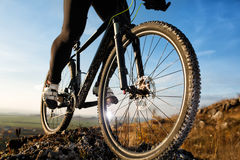 Closeup feet athlete mountainbiker and wheels of a sports bicycle Stock Photo