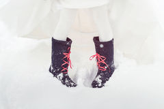 A closeup of the feet of the bride in felt boots on snow. Accessories for a stylized Russian wedding Stock Images