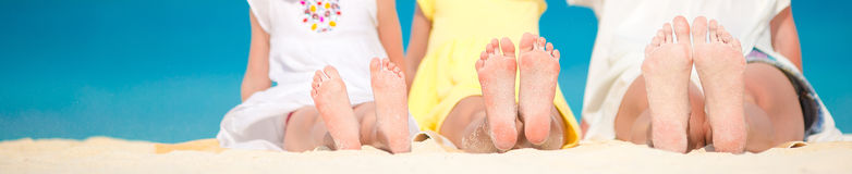 Closeup of the feet of family on the white sandy beach Royalty Free Stock Images