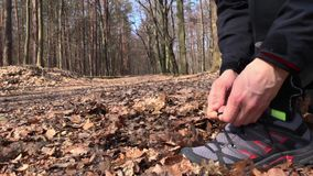 Closeup of feet of male runner tying running shoe and starts workout. stock video footage