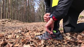 Closeup of feet of male runner tying running shoes and checking his smartwatch. stock video