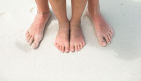 Closeup feet of a mom and kid on white sand beach Royalty Free Stock Image