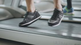 Closeup feet moving on treadmill in fitness gym. Black fit shoes jumping on running machine. Athletic legs training cardio exercises in sport club stock footage
