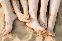 Closeup of feet row lying in line at summer beach royalty free stock image