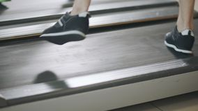 Closeup feet running back on treadmill in fitness gym. Black sneakers jumping on running machine. Fit legs training cardio exercises in sport club stock video