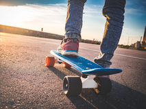 Closeup of the feet on the skateboard on the pavement Stock Photos