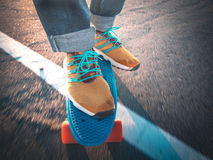 Closeup of the feet on the skateboard on the pavement Stock Photography
