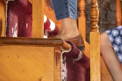 Closeup of feet of two girls or women climbing wooden stairs with floral carpet - selective focus and bokeh stock photo