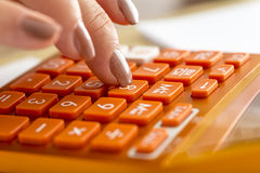 Closeup of female accountant pressing number eight on orange des. Ktop calculator in an accounting, research or education concept Royalty Free Stock Images