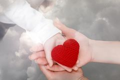 Female adult hands with child palm holding a knitted heart. A closeup of female adult hands holding a child palm with bright red knitted heart on it at grey sky royalty free stock photography