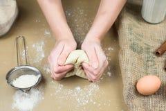 Closeup of female baker's hands kneading dough in bakery. Close up Stock Photos