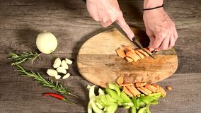 Closeup of female chef hands slicing peeled carrots on a wooden cutting board next to sliced vegetables. The concept of. Vegetarianism stock footage