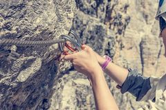 Closeup of female climber attaching via ferrata set to steel cable. royalty free stock images