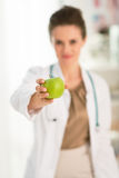 Closeup on female doctor giving green apple stock photos