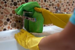 Female employee doing cleaning in bathroom. Closeup of female employee of cleaning company doing cleaning in the bathroom and wiping sink with rag royalty free stock photos