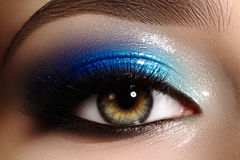 Closeup female eye with beautiful fashion bright make-up. Beautiful shiny blue eyeshadow, wet glitter, black eyeliner. Perfect eyebrows shape royalty free stock photos