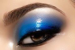 Closeup female eye with beautiful fashion bright make-up. Beautiful shiny blue eyeshadow, wet glitter, black eyeliner royalty free stock image