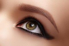 Closeup Female Eye with Dark Make-up, great Shapes Brows. Celebrate Makeup, Luxury Eyeshadows. Fashion Eyeliner, pencil. Macro of beautiful eye. Good vision royalty free stock photo