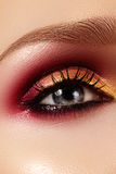 Closeup female eye with fashion bright make-up. Beautiful gold, red eyeshadow, glitter, black eyeliner. Shape Eyebrows Royalty Free Stock Images