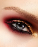 Closeup female eye with fashion bright make-up. Beautiful gold, red eyeshadow, glitter, black eyeliner. Shape Eyebrows Royalty Free Stock Photo