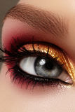 Closeup female eye with fashion bright make-up. Beautiful gold, red eyeshadow, glitter, black eyeliner. Shape Eyebrows. Closeup female eye with fashion bright stock images
