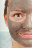 Closeup female face with clay mud facial mask. Spa beauty treatment and skin care. Closeup part of female face with clay mud facial mask Royalty Free Stock Image
