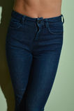 Closeup on female with fitness body in jeans. Blue color Royalty Free Stock Photos