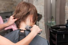 Closeup on female hairdresser cutting hair of man client using trimmer. Stock Photo