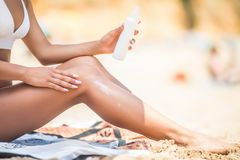 Closeup on woman Hand applying sunscreen creme on Leg. Skincare. Sun protection sun cream, on her smooth tanned legs. royalty free stock image