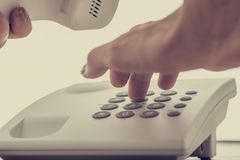 Closeup of female hand dialing a telephone number Stock Photo