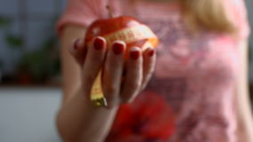 Female hand holding red apple with measuring tape stock video