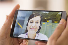 Closeup of a female hand holding a smart phone during a skype vi Royalty Free Stock Photos