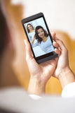 Closeup of a female hand holding a smartphone during a skype vid Stock Photo