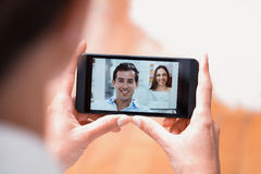 Closeup of a female hand holding a smartphone during a skype vid Stock Photos