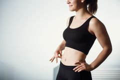 Closeup Of Female Hand Pinching Fit Pumped Belly royalty free stock image