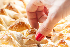 Closeup of female hand reaching for pastry Royalty Free Stock Image
