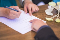 Closeup of Female Hand Signing Wedding Contract Royalty Free Stock Images