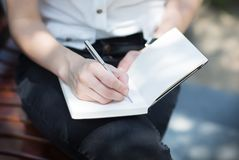 Closeup of a female hand writing on an blank notebook with a pen. royalty free stock image