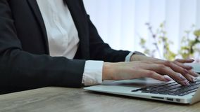 Closeup of a female hands busy typing on a laptop stock footage