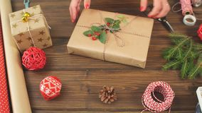 Closeup female hands decorating gift red boxes for Christmas Holiday. Present packaging ideas.  stock footage