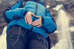 Closeup of female hands forming a hearth on her belly in nature. Motherly love outdoor Stock Image